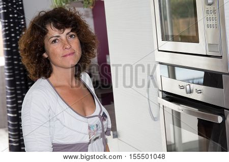 a Woman at home using microwave oven