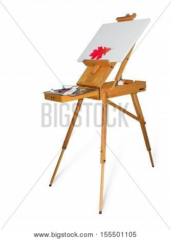 Wooden easel tripod design with red oak leaf on the blank canvas and painting tool on a light background