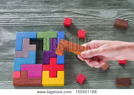 The concept of logical thinking. Wooden geometric shapes. Tetris toy wooden blocks on a wooden background.