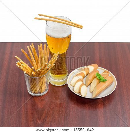 Beer glass with lager beer salty hard crispy mini pretzels shaped as sticks and sliced smoked processed cheese on a saucer on a wooden surface on a light background