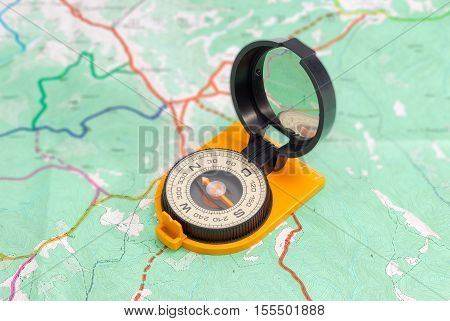 Dry magnetic compass with mirror of sighting mechanisms on a tourist topographical map