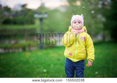 Funny baby girl in a yellow coat and pink hat and knitted scarf playing in a beautiful park