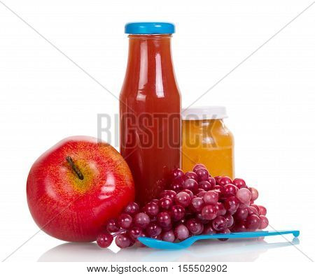 A bottle of juice, pink grapes, a jar of fruit puree, apple and a plastic spoon isolated on white background.