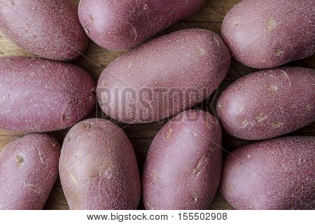 Red big imperfect potatoes on wooden cutting board from above