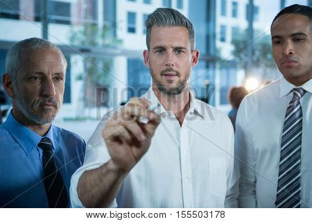 Businessman writing with marker on glass in office