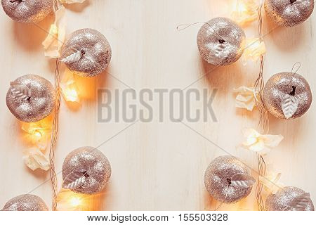 Christmas silver apples decoration and lights burning on a beige wooden background. Xmas background.