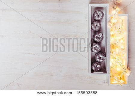 Christmas silver apples and lights burning in boxes on a wooden white background. Top view. Xmas background.