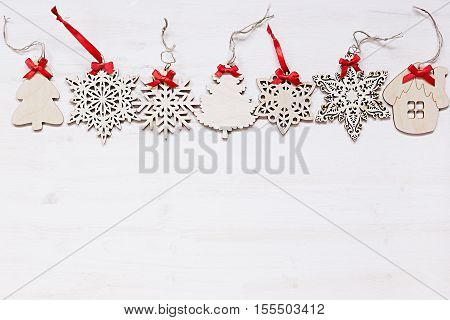 Christmas soft beige wooden snowflakes on a wood white background. New Year frame background.