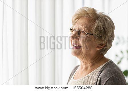 Portrait of an elderly woman looking through a window