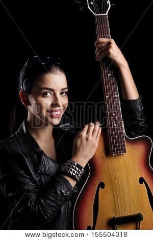 Young woman with a guitar isolated on black background