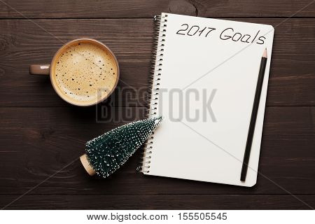 Cup of coffee and notebook with goals for 2017. Planning and motivation for the new year concept. Top view.