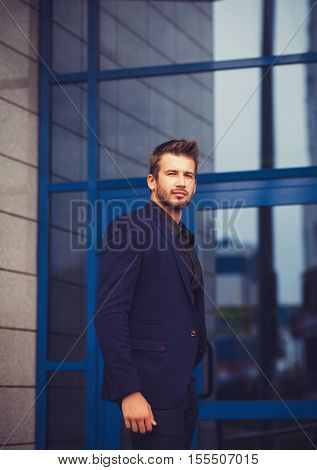 Portrait of a businessman in blue suit near office