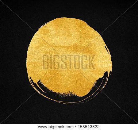 Golden paint stain on black paper background. Gold circle texture.