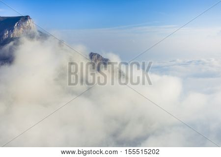 Picturesque view of a layer of white clouds below the mountain peaks in the Bucegi Mountains from the Carpathians in Romania. Mountain scenic landscape above the clouds.