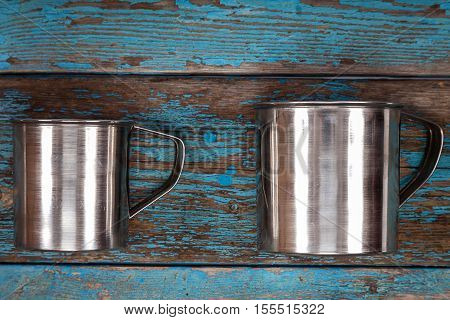 Metal mugs on a wooden background. Kitchenware. Tea accessories.
