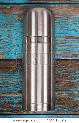 Metal thermos on a wooden background. Kitchenware. Tea accessories.