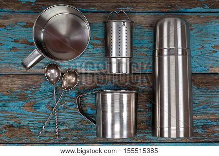 Metal thermos strainer mugs and spoons on a wooden background. Kitchenware. Tea accessories.