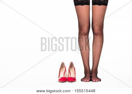 Heel shoes on white background. Legs in stockings. Emphasize your sexuality. Look feminine and beautiful.