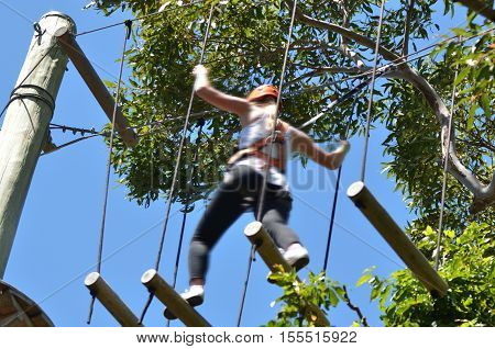 Young woman walks on tree logs during a treetop adventure climbing. Woman risk and challenge concept. copy space