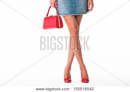 Legs in heels and handbag. Short blue jeans skirt. How to emphasize femininity. Look fashionable this summer.