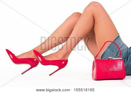 Handbag and legs in heels. Red purse and shoes. Dress to impress. Elegant footwear from new collection.