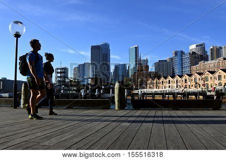 Young couple walks along Sydney Circular Quay wharf in at Sydney Cove near The Rocks in Sydney New South Wales Australia