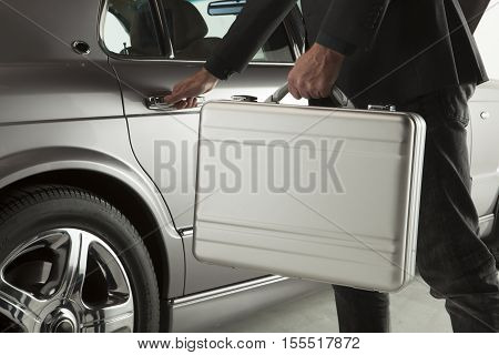Hand on handle. Close-up of man in formalwear opening a car door with a briefcase