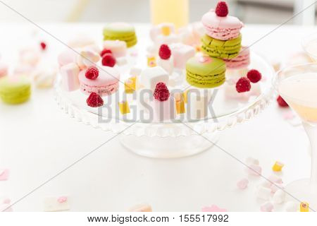 Colorful sweet macaroons, marshmellows and fresh berries on the plate