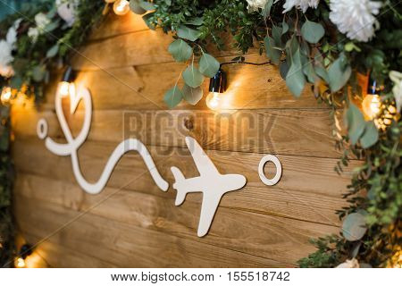 white plane on wooden boards decorated with flowers. distance and love. journey.