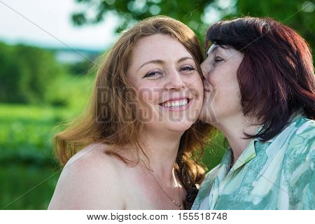 happy mom kisses daughter in the garden