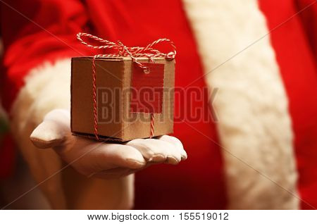 Santa Claus gloved hands holding giftbox. Christmas