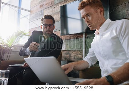 Two young man sitting in office and discussing business using laptop. Business colleagues working on laptop during meeting.