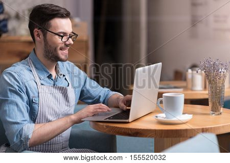 Great job. Satisfied attractive young man smiling and working on laptop while sitting by the table.