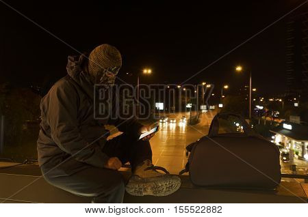 Terrorist in the center of a city sitting on a bridge. Night shot. Long exposure