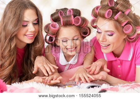 portrait of happy  Mother and  daughters in hair curlers  at home