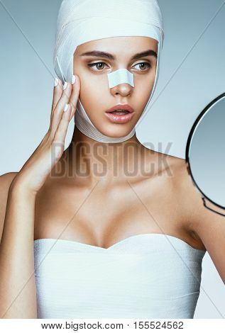 Young woman after plastic surgery looking in mirror and touching her cheekbone. Photo of woman wrapped in medical bandages. Beauty concept