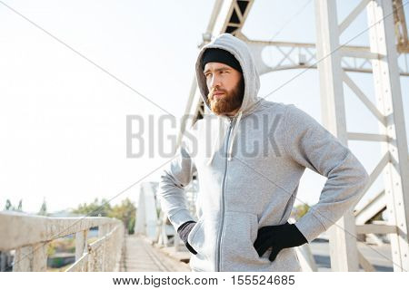 Portrait of a young sport athlete man in hoodie standing at the urban bridge with hands on hips