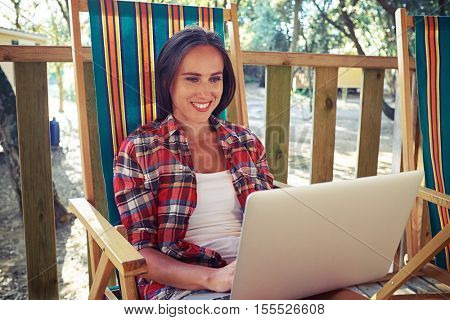 Close-up of pleased woman who is texting with friends via laptop. Sitting on a comfortable summer beach chair. Communicating with people, using laptop. Wearing casual checked shirt and denim shorts
