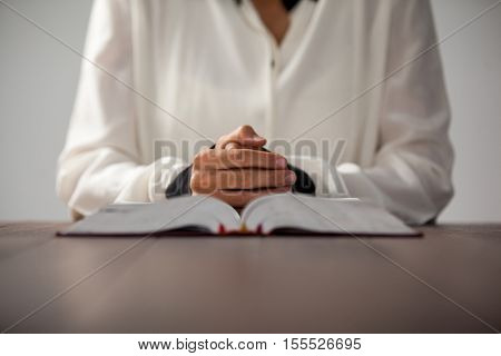Woman sitting at desk with a bible