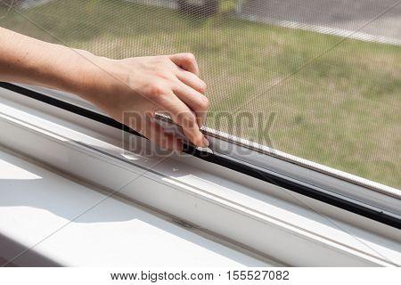 Installing mosquito nets for plastic windows closeup