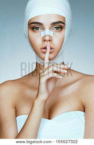 Diva keeping secret of her plastic surgery. Photo of perfect girl with bandage on her face after facelift. Beauty concept