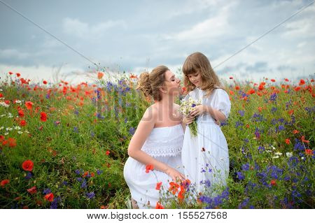 Brunet mother with cute young daughter on a poppy field with white bouquet of meadow flowers