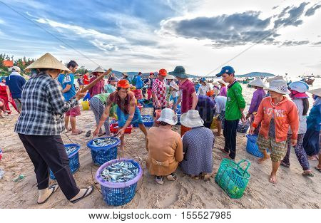 Phan Thiet, Vietnam - July 26th, 2016: Fish market session seas scene people gathered inside basket fish sale, strenuous rowing fishermen fish brought ashore fishing village in Phan Thiet, Vietnam