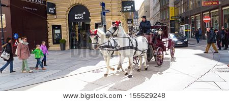 Vienna, Austria - April 3, 2015: City center panoramic street view, people walking and fiaker with white horses in Vienna, Austria