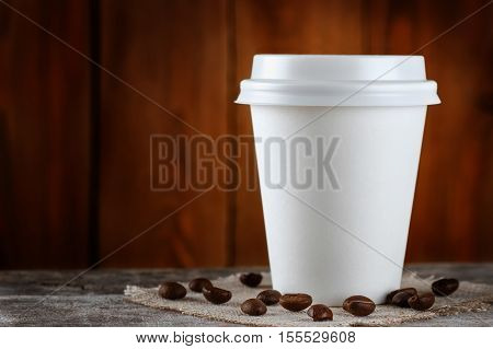 paper cup of coffee on wooden background with copy space. Coffee on table on wooden background. Takeaway coffee. Coffee to go. Coffee. Disposable cup of coffee with closed lid