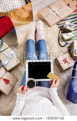 Christmas online shopping top view. Female buyer touch screen of tablet with copy space, holds credit card. Woman has coffee, buy presents, prepare to xmas, among gift boxes and packages. Winter sales