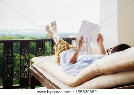 Rear view of asian man relaxing on a sofa and holding book on bed a beautiful green background view at home terrace. Relaxing concept.