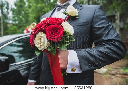 groom holding a bouquet of white daisies, bouquet of white flowers in male hands