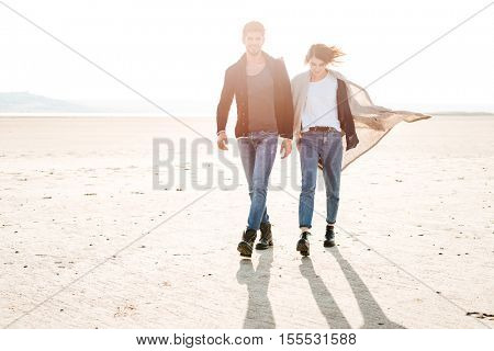 Full length portrait of smiling happy couple walking along seashore in sunlight