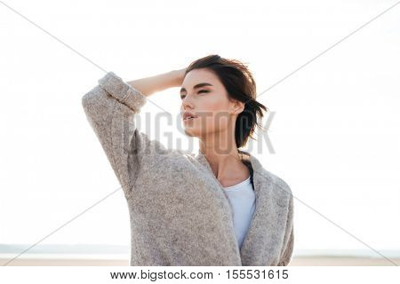 Beautiful relaxed young woman standing and posing on seashore and looking away